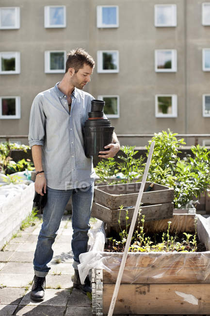 Young man with stacked flower pots standing at urban garden — Stock Photo