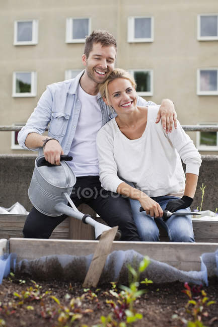 Happy young man holding watering can sitting with woman at urban garden — Stock Photo