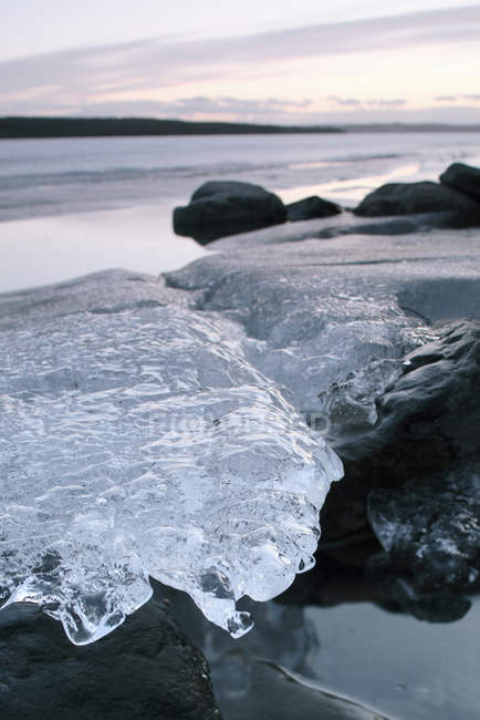 Close-up of clear ice on rocks by river — стокове фото