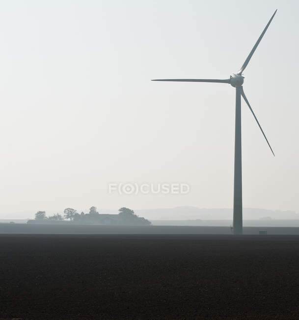 Distant view of  Wind turbine in foggy landscape — Stock Photo