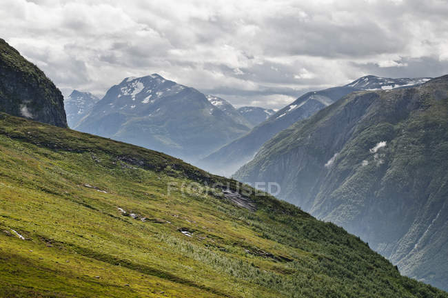 Clouds over mountain range and green hill in foreground — Foto stock