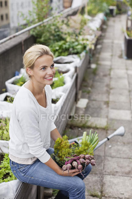 Thoughtful young woman with freshly harvested vegetables at urban garden — Stock Photo