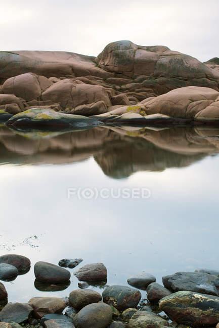 Скелястий берег озера і галька передньому плані — стокове фото