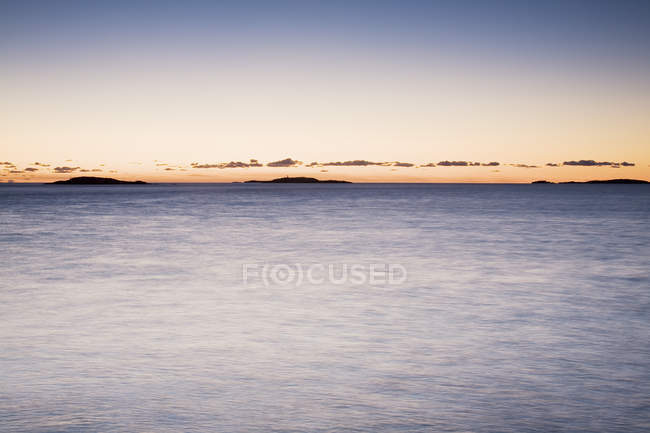 Calm and silhouettes of islands on horizon at sunset — Stock Photo