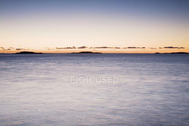 Спокойствие и силуэты островов на горизонте на закате — стоковое фото