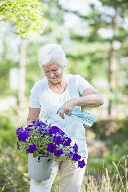 Happy senior woman spraying water on flower plant — Stock Photo