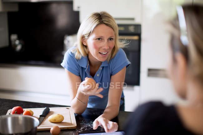 Mujer conversando con un amigo mientras prepara comida en la cocina - foto de stock