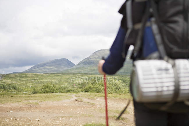Midsection of woman holding hiking pole and mountains at background — Stock Photo