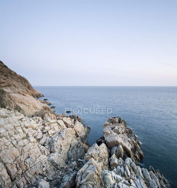 Picturesque view of rocky shores in calm sea and empty horizon on background - foto de stock