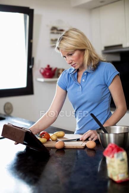 Mujer adulta media usando receta en mesa digital y haciendo comida en la cocina - foto de stock