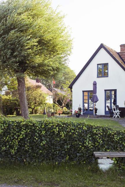 Jardín con césped verde cerca privada casa de dos pisos - foto de stock