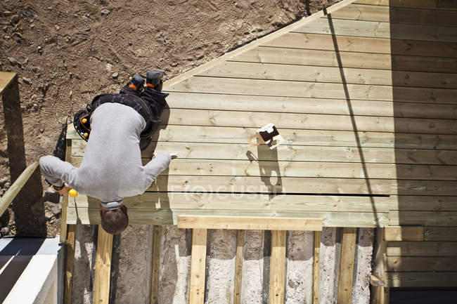 Overhead view of man in working clothes drilling floorboard — Stock Photo
