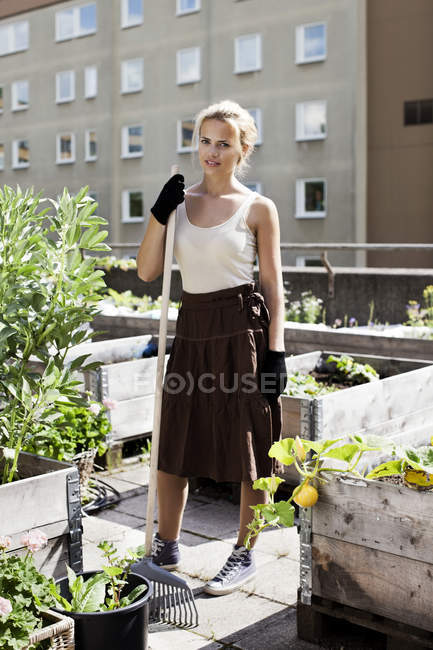 Portrait of young woman with gardening fork standing at urban garden — Stock Photo