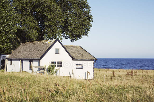 Tranquil scene of house with sea in background — Stock Photo