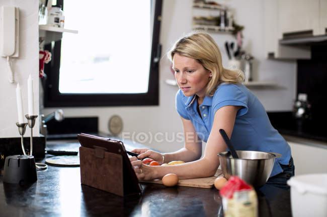 Mujer que busca recetas en tableta digital en la cocina - foto de stock