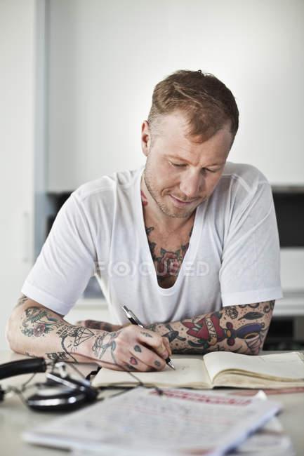 Tätowierter Mann schreibt in Buch am Schreibtisch — Stockfoto