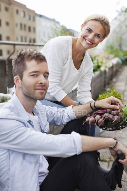 Happy young couple holding freshly harvested vegetable at urban garden — Stock Photo