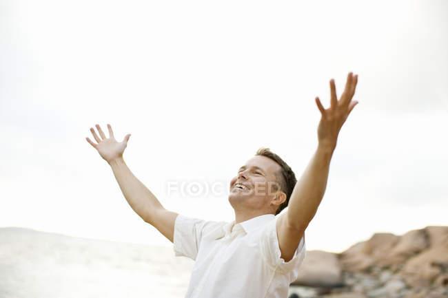 Uomo eccitato con le braccia distese sulla riva — Foto stock