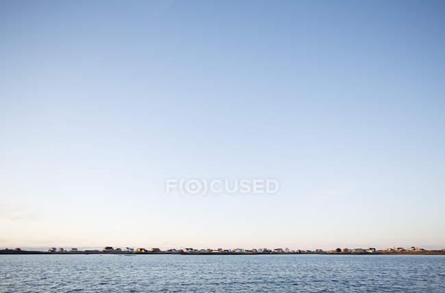 Vista distante da costa com cidade e céu claro do mar — Fotografia de Stock