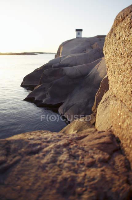 Маяк на скелястому березі спокійне море — стокове фото