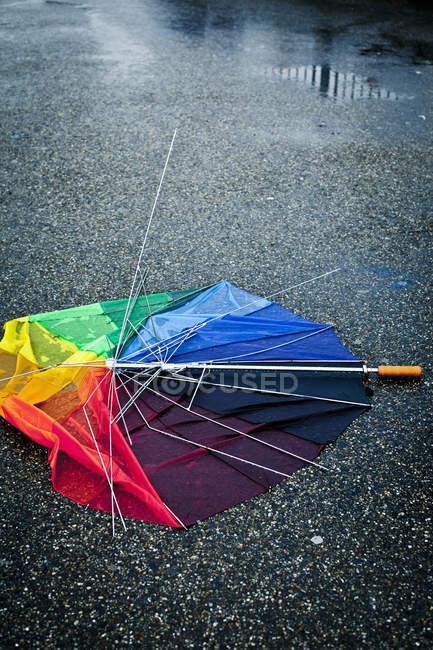 Multi colores paraguas roto en la calle - foto de stock