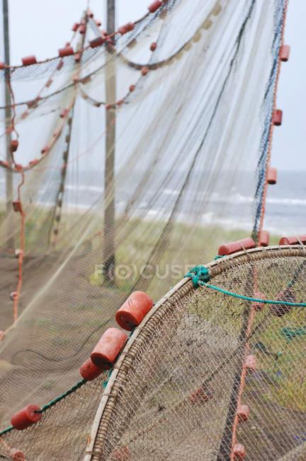 Filet de pêche accroché pour le séchage sur côte herbeux — Photo de stock