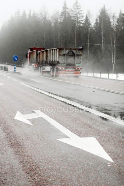 LKW auf der Straße mit Wegweiser im Vordergrund — Stockfoto