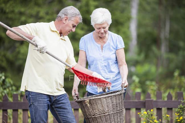 Seniorenpaar mit Harke und Korb im Garten — Stockfoto