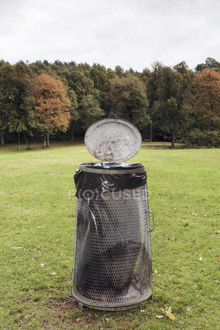 Garbage can in park on autumn trees background — Stock Photo