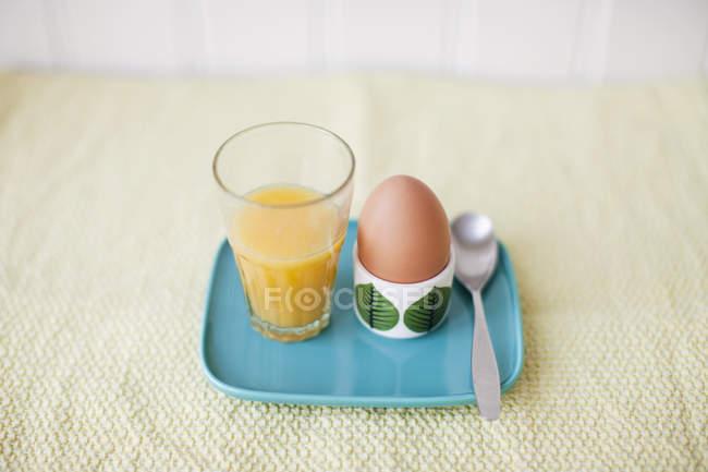 Стакан сока и вареное яйцо синий лоток — стоковое фото