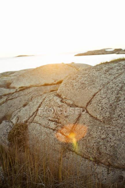 Pôr do sol sobre o mar com rocha em primeiro plano — Fotografia de Stock