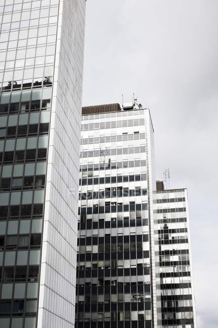 Vista de ángulo bajo de edificios de oficinas bajo cielo nublado - foto de stock