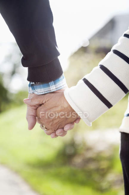 Partial view adult couple in casual clothes holding hands — Stock Photo