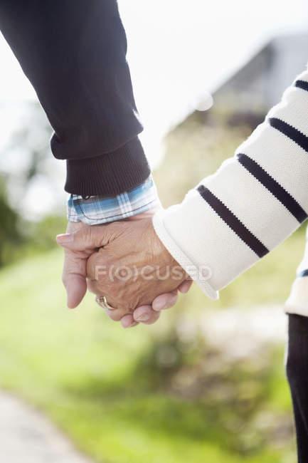 Couple adulte vue partielle dans des vêtements décontractés, main dans la main — Photo de stock