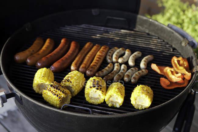 Ковбаси та corncobs на грилі — стокове фото
