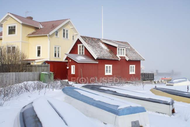 Barcos, coberto de neve perto das casas em dia de inverno — Fotografia de Stock