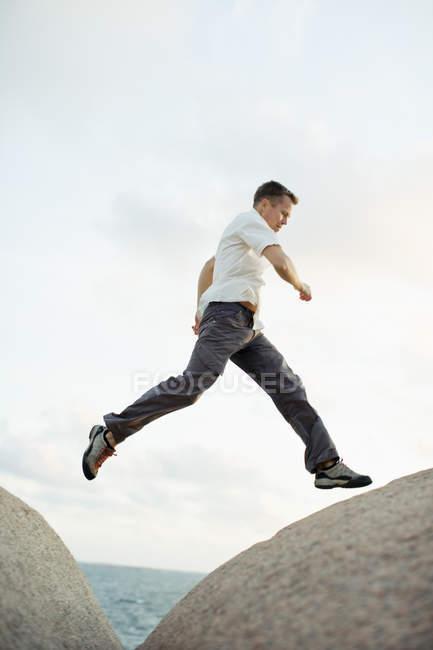 Full length of man jumping over rocks — Stock Photo