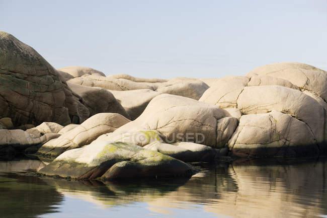 Скелястий берег озера і спокійній воді на передньому плані — стокове фото