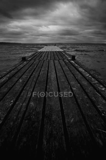 Langer Holzsteg unter dramatischem Himmel, Rücken und weiß — Stockfoto