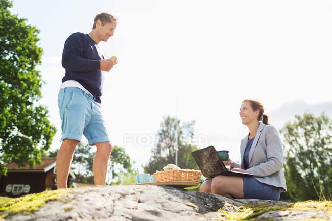 Vista lateral do homem maduro falando com empresária usando laptop no rock — Fotografia de Stock
