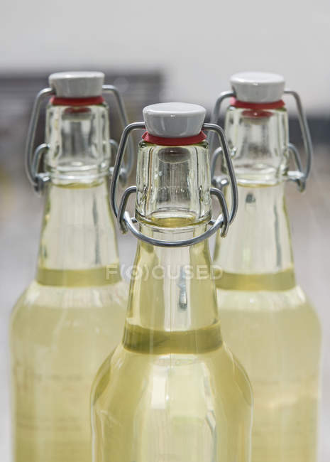 Yellow juice in glass bottles with unusual covers — Stock Photo