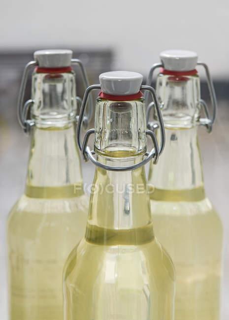 Желтый сок в стеклянные бутылки с необычной охватывает — стоковое фото