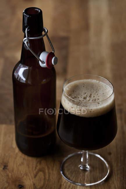Бутылка пива судов и стекла на деревянный стол — стоковое фото