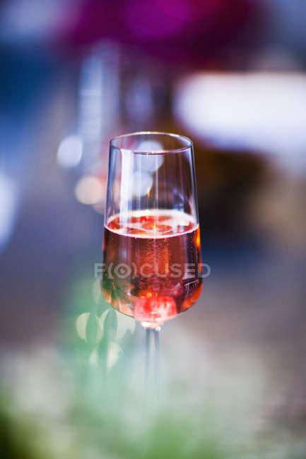 Fuoco selettivo del bicchiere riempito a metà con la bevanda rossa — Foto stock