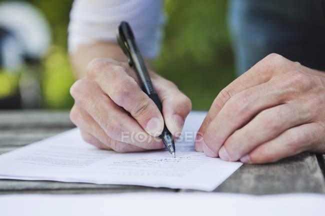 Середині розділі Перегляд чоловічої руки робить примітки в документі за перо — стокове фото