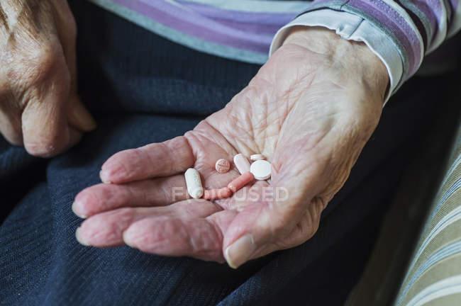 Midsection de la femme âgée tenant des pilules tout en étant assis à la maison — Photo de stock
