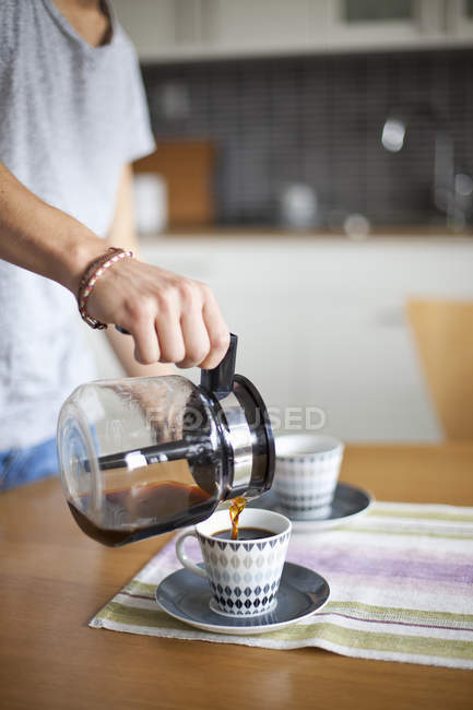 Midsection of man pouring coffee in cup at table — Stock Photo