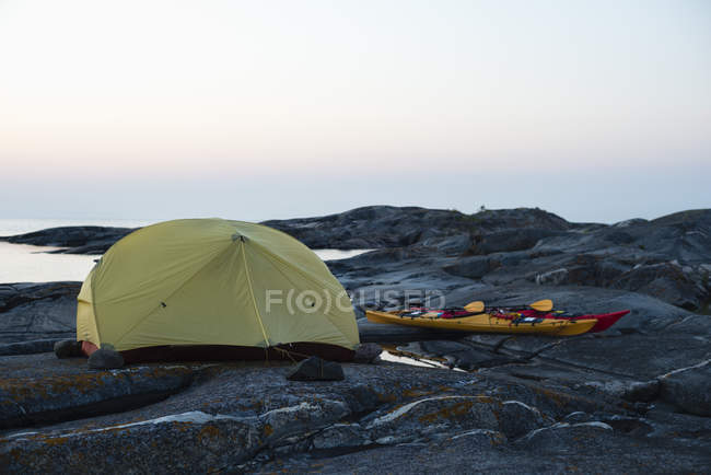 Байдарки і намет на скелястому березі моря проти неба — стокове фото