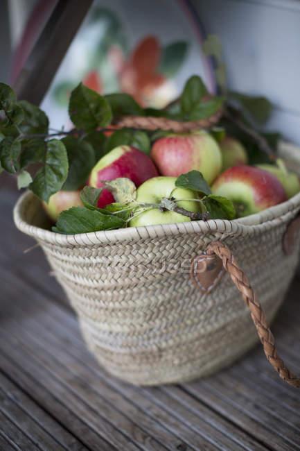 Яблоки в плетеной сумке на столе — стоковое фото