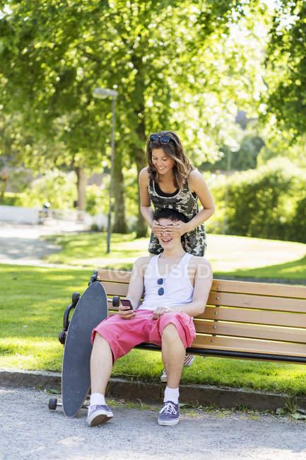 Smiling girlfriend covering boyfriend's eyes in park — Stock Photo